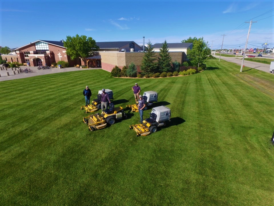 aerial shot of four lawn care workers and Walker mowers on a commercial site